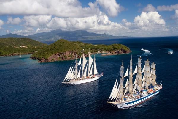Dos barcos con grandes velas navegando en un bello mar azul