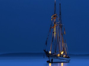 Embarcación en la inmensidad del mar al caer la noche