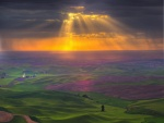Rayos de sol filtrándose entre las nubes iluminando campos verdes