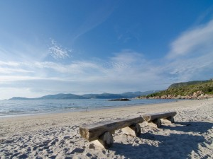 Postal: Bancos de madera sobre la arena de una playa