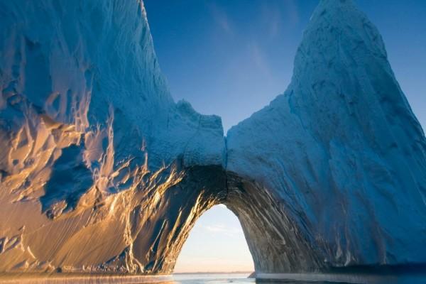 El sol iluminando una pared del iceberg a través de un arco de hielo