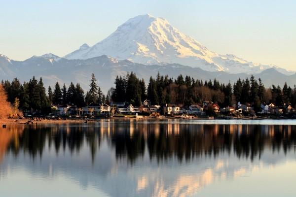 Montaña y casas reflejadas en un lago