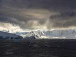 Sol iluminando las montañas entre las nubes grises
