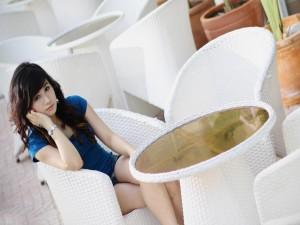 Muchacha sentada en una silla blanca