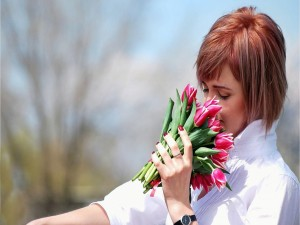 Postal: Chica oliendo tulipanes
