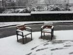 Nieve sobre unos asientos urbanos
