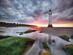Faro en una playa al amanecer