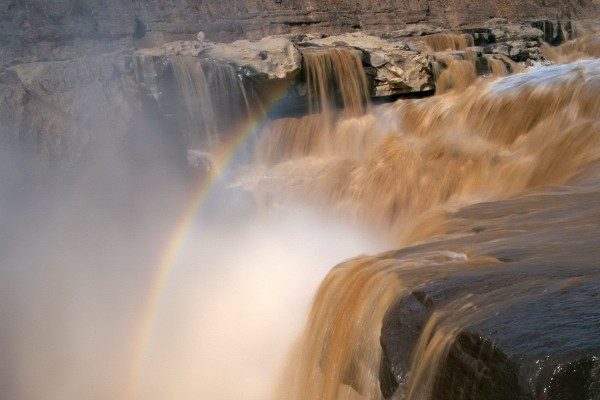 Arcoíris sobre las cascadas de un río caudaloso