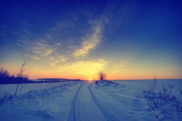 Sol en el horizonte de un paisaje nevado