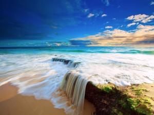 Postal: El agua del mar formando una pequeña cascada en una playa