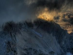 Postal: Espesas nubes cubriendo unas montañas