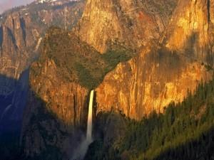 Sol iluminando el gran salto de agua y las paredes rocosas