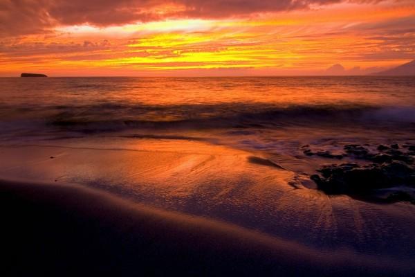 Amanecer anaranjado sobre una playa