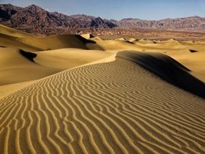 Postal: Dunas y montañas en un desierto