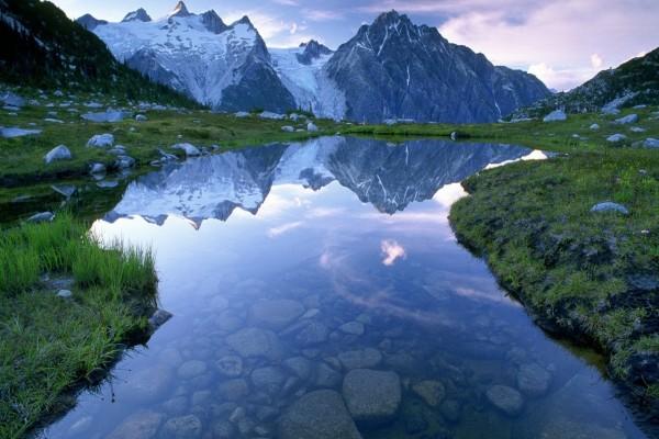 Montañas reflejadas en las aguas transparentes de un pequeño lago