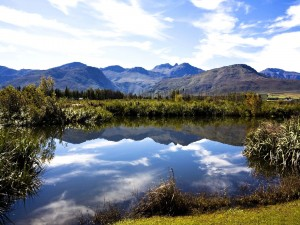 Postal: Montañas reflejadas en las aguas de un río