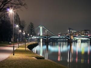 Postal: Puente iluminado sobre un río