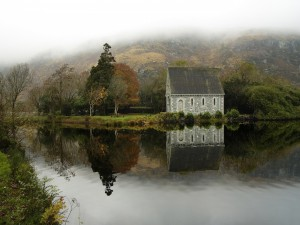 Postal: Casa de piedra reflejada en un río
