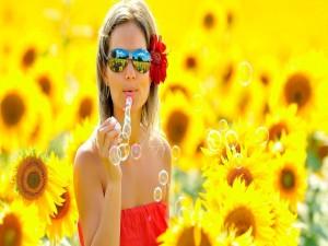 Mujer haciendo pompas en un campo de girasoles