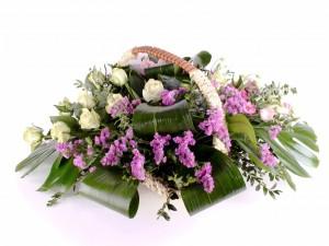 Arreglo floral con eustomas y rosas en una cesta