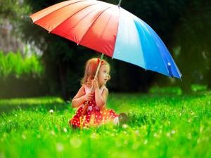 Niña con un paraguas de colores en un verde prado