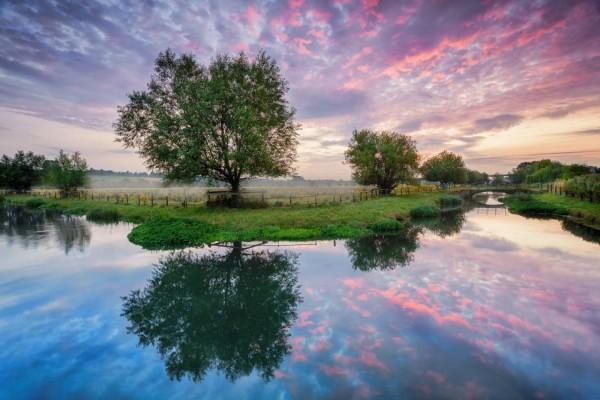 Las primeras luces del amanecer reflejadas en un río