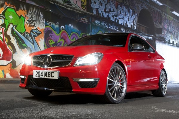 Un Mercedes rojo con las luces encendidas