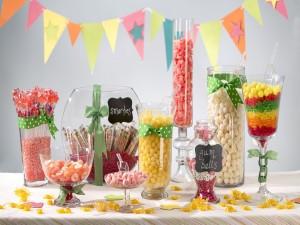 Fiesta de cumpleaños con banderines y recipientes llenos de golosinas