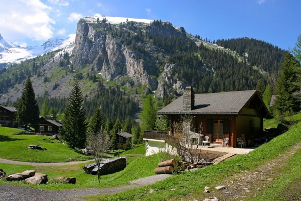 Cabaña de madera en un paisaje primaveral de los Alpes