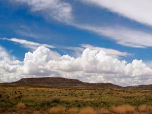 Postal: Nubes blancas sobre un paisaje desértico