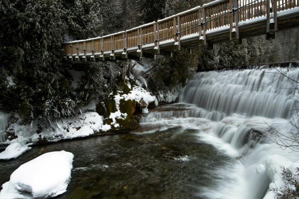 Puente sobre una cascada invernal