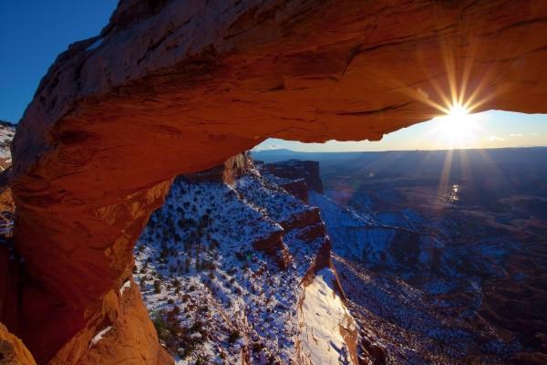 El sol brillando sobre un arco de piedra