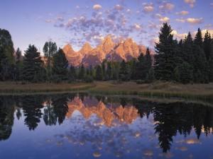 Pequeñas nubes y montañas reflejadas en el agua