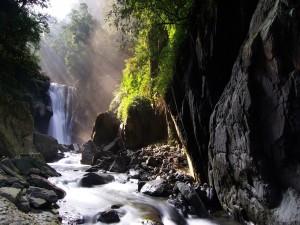 Postal: Rayos de sol iluminando una cascada