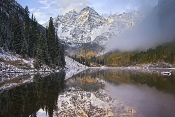 Niebla y montañas reflejadas en un lago