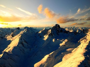 Postal: Hermoso amanecer sobre unas montañas cubiertas de nieve
