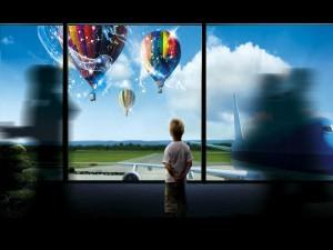 Niño admirando unos globos que vuelan sobre un aeropuerto