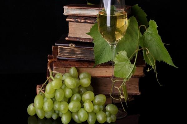 Una mesa con libros y buen vino de uva blanca
