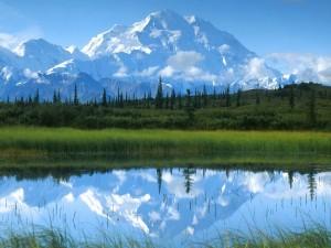 Postal: Bonitas montañas nevadas reflejadas en un río