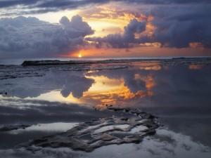 Amanecer reflejado en aguas poco profundas