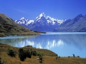 Postal: Un bonito lago azul junto a grandes montañas