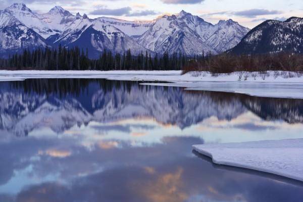 Montañas reflejadas en un lago helado