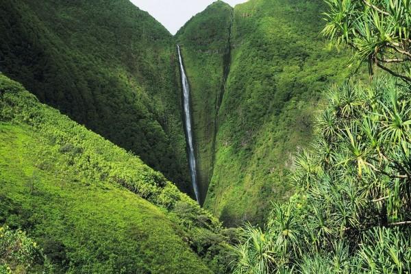 Cascada fluyendo sobre unas montañas verdes