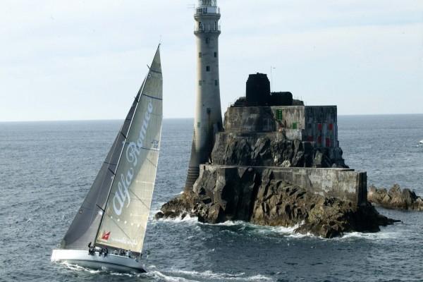 Barco navegando junto a un faro