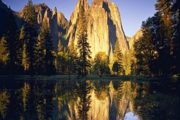 Árboles y rocas reflejados en un lago