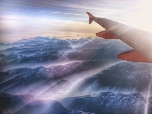 Postal: El ala de un avión sobre unas montañas