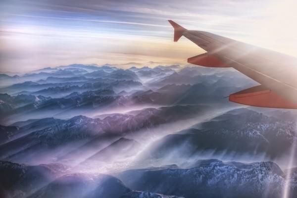 El ala de un avión sobre unas montañas