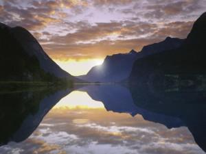 Postal: Sol al amanecer reflejado en un lago