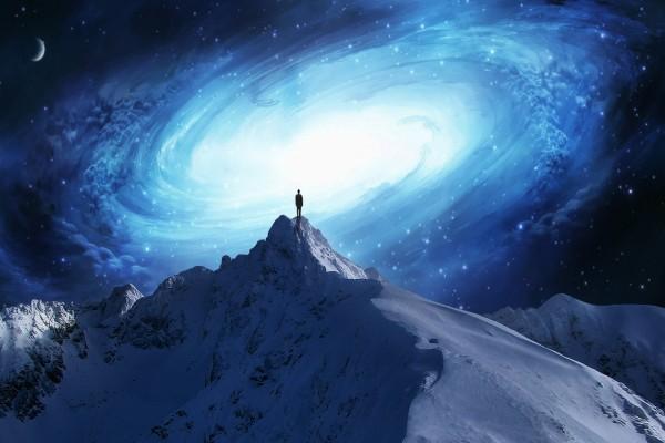 Hombre en la cima de una montaña contemplando una galaxia