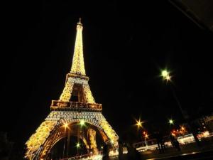 Postal: La Torre Eiffel iluminada en la noche parisina
